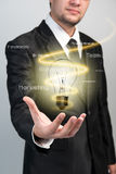 Businessman with idea light bulb. In hand stock images