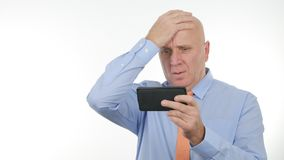 Businessman image Reading Bad News on Smartphone and Gesticulate Nervous.  royalty free stock images
