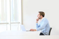 Businessman imagining new strategy. Thoughtful businessman working on laptop in business room Royalty Free Stock Image