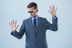 Businessman imagining while using virtual reality glasses Stock Photos