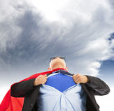 Businessman imitate superman to pull his t-shirt open. With dark cloud Stock Photos
