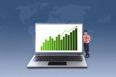 Businessman and increasing bar chart on laptop Royalty Free Stock Photography