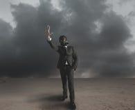 Businessman indicates radiation. Hazard in a desert royalty free stock images