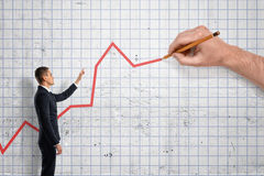 Businessman indicating large hand how to draw graph. Businessman indicating a large hand how to draw a graph. Investment and finance. Successful management royalty free stock photos