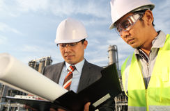 Businessman and industrial engineer. Businessman and oil refinery engineer  discussing a new project with large oil refinery background Stock Image