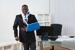 Businessman With Injuries In Office Stock Image