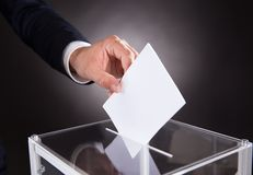Businessman inserting ballot in box on desk. Cropped image of businessman inserting ballot in box on desk against black background Stock Photos