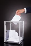 Businessman inserting ballot in box on desk Stock Image
