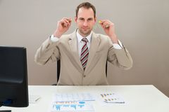 Businessman inserting earplug in ears Royalty Free Stock Image