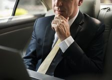 Businessman inside a car working on his laptop Royalty Free Stock Images