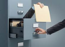 Fast file search. Businessman inside a filing cabinet giving a file to an office clerk: fast file search and efficiency concept royalty free stock image