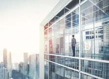 Businessman inside the house looking at city. Businessman standing inside the house looking at city Stock Photography