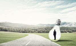Businessman inside light bulb Stock Image