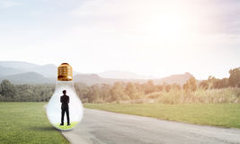 Businessman inside light bulb Stock Photography