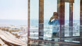 Businessman inside office building talking on mobile phone. Businessman standing by window and talking on mobile phone. Man standing inside office building and Royalty Free Stock Photos