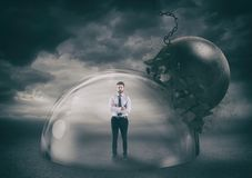 Businessman safely inside a shield dome during a storm that protects him from a wrecking ball. Protection and safety. Businessman inside a transparent sphere stock image