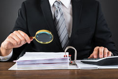 Businessman Inspecting Invoice With Magnifying Glass Stock Photos