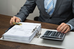 Businessman inspecting receipts in office stock photos
