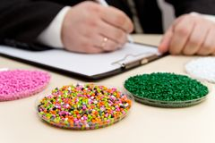 Businessman inspects plastic pellets for industry. Plastic raw materials in granules . Polymer, plastic resin. The dye in the granules of polypropylene and stock image