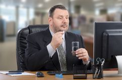 Administrator takes a pill during e-health doctor appointment. Businessman intends to swallow white pill during telehealth doctor appointment. Mature man in Royalty Free Stock Image