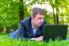 Businessman intently working on a laptop. On the grass Stock Photography