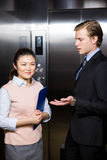 Businessman interacting with businesswoman. In elevator Stock Images