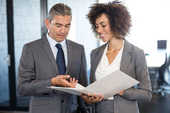 Businessman interacting with colleague. Businessman looking into a document and interacting with colleague Stock Photo