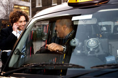 Businessman interacting with taxi driver Stock Photo