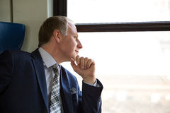 Businessman interested in what he sees through window Stock Images