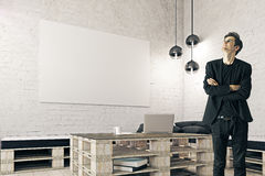 Businessman in interior with blank banner. Smiling young businessman looking up in loft interior with laptop on wooden coffee table and blank banner on brick Stock Photography