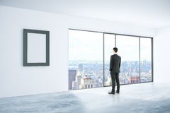 Businessman in interior with frame. Businessman looking out of window in concrete interior with blank picture frame and city view. Mock up, 3D Rendering Royalty Free Stock Photos