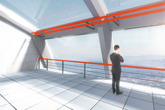 Businessman in interior. Thinking businessman in white and red futuristic interior with landscape view. 3D Rendering Stock Photo