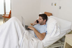 Businessman intern as patient in hospital suffering disease and working happy and relaxed at clinic bed. Young businessman intern as patient in hospital royalty free stock photo