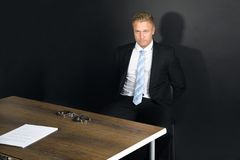 Businessman In Interrogation Room. Portrait Of Young Businessman Sitting In Interrogation Room Royalty Free Stock Photo