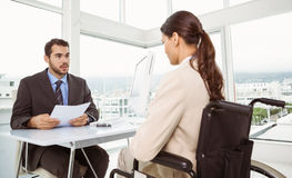 Businessman interviewing woman in office Stock Image