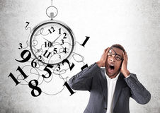 Businessman intimidated by deadlines. Overwhelmed African American businessman holding his head with both hands and screaming. Large stopwatch with numbers Royalty Free Stock Images