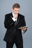 Businessman is intrigued by the news he is reading on his tablet pc Stock Photos