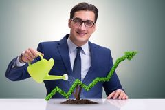 The businessman in investment concept watering financial line chart. Businessman in investment concept watering financial line chart Royalty Free Stock Image