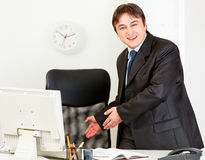 Businessman inviting to sit on office chair. Friendly modern business man inviting to sit on office chair Royalty Free Stock Image