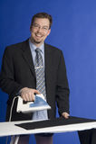 Businessman ironing. Businessman starting to iron suits trousers Royalty Free Stock Photography