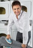 Businessman Ironing Jeans In Laundry Stock Images