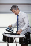 Businessman ironing pants Royalty Free Stock Image