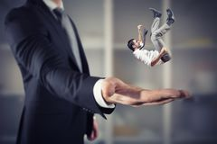 Free Businessman Is Saved From A Big Hand. Concept Of Business Support And Assistance Royalty Free Stock Photo - 111447635