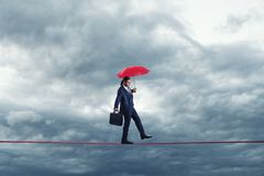 Free Businessman Is Walking On A Thiny Rope, Metaphoring Risky Business Life An Capability Of Solving Problems In Balance. Stock Photos - 168423023