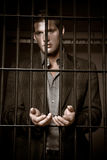 Businessman in jail. A caucasian businessman sitting in jail handcuffed Stock Image