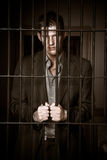 Businessman in jail. A caucasian businessman sitting in jail handcuffed Royalty Free Stock Photos