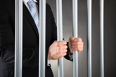 Businessman in jail. Close-up Of Businessman In Jail Holding Metal Bars Royalty Free Stock Images