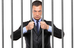 A businessman in jail holding bars. Isolated on white stock photos
