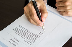 Businessman or job seeker signing on resume form. Royalty Free Stock Photography