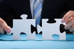 Businessman joining puzzle pieces at desk Royalty Free Stock Photography